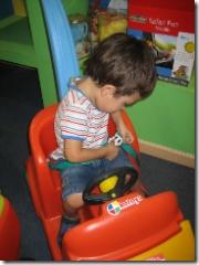 child driving in plastic toy car