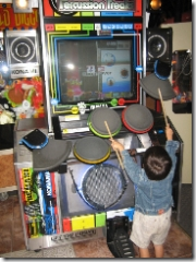 child playing rockband at arcade