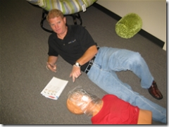 man laying on ground with cpr dummy