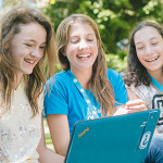 girls working at computer coding laughing